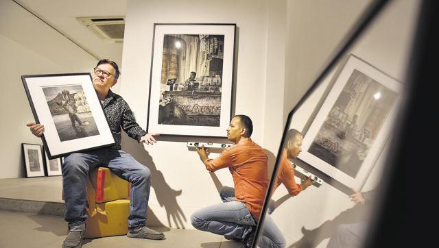 Photographer Waswo X. Waswo and Rajesh Soni, who hand-colours his black and white pictures, setting up their exhibition in a gallery in Lado Sarai.