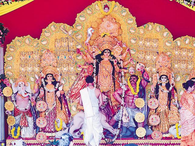 Dhakis perform in front of a Durga Puja pandal.