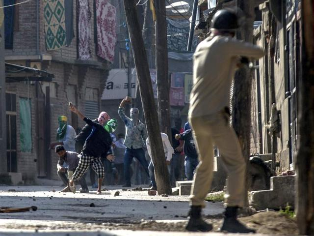 Kashmiri protesters throw stones at a policeman as he prepares to fire a pellet gun during a protest in Srinagar.