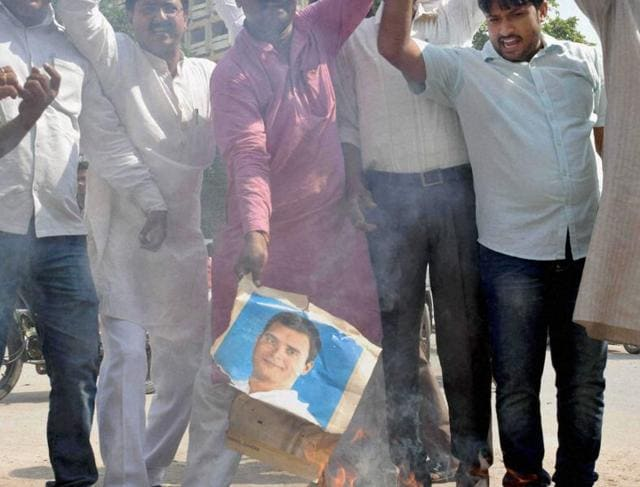 Allahabad: BJP workers burn the photographs of Congress vice-president Rahul Gandhi in Allahabad on Saturday.