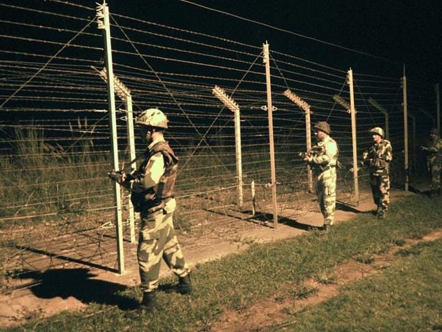 Border Security Force soldiers stand guard during a night patrol near a fence at the India-Pakistan International Border.