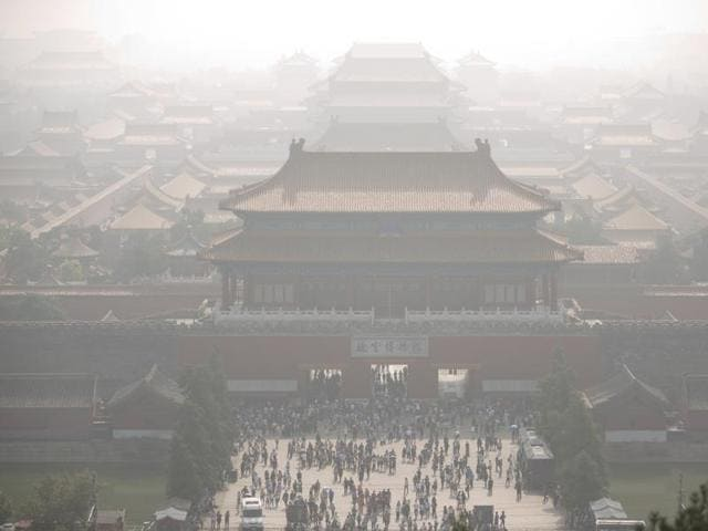 Tourists exit the Forbidden City on a day with high levels of air pollution in Beijing, Monday, Oct. 3, 2016.