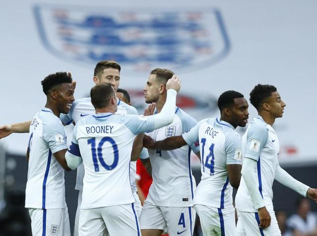 Dele Alli celebrates with teammates after scoring England's second goal.