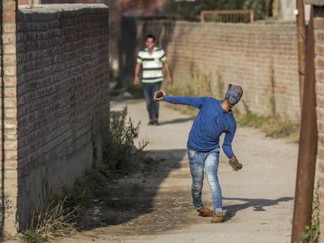 A protester throws rocks at government forces after the police stopped the funeral procession of Junaid Ahmed, a 12-year-old boy in Srinagar.