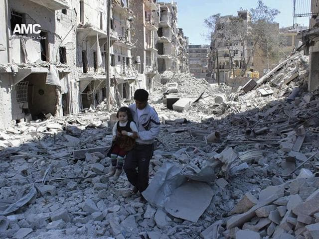 A Syrian man holding a girl as he stands on the rubble of houses that were destroyed by Syrian government forces air strikes in Aleppo, Syria.