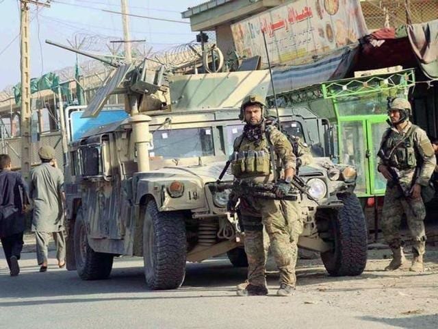 Afghan security forces keep watch in front of their armoured vehicle in Kunduz city.