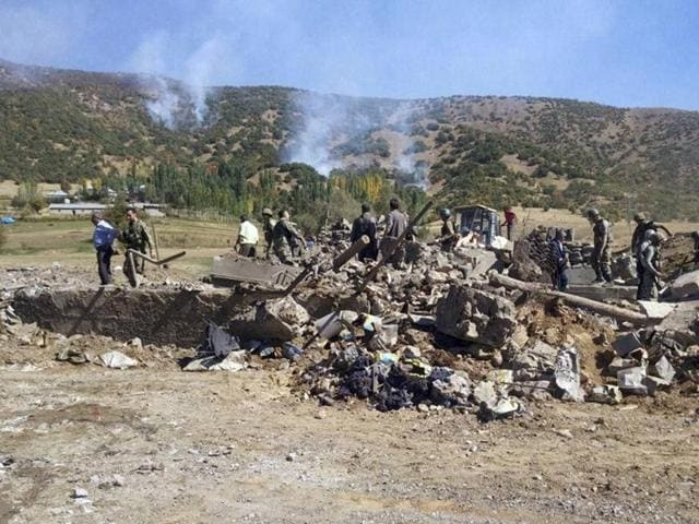 Soldiers and locals at the scene of a car bomb attack in Semdinli, Turkey, on Sunday. Kurdish militants detonated a car bomb Sunday outside a military checkpoint in southeast Turkey, killing ten soldiers and eight civilians, Turkish Prime Minister Binali Yildirim said.