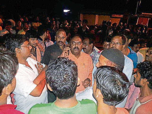 Former BJP MLA Bhagat Netam (talking over phone) outside the Baihar police station in Balaghat on the night of Sept 25.