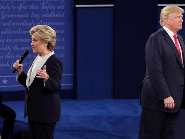 Democratic presidential nominee former Secretary of State Hillary Clinton (left) speaks as Republican presidential nominee Donald Trump looks on during the town hall debate at Washington University on Sunday.