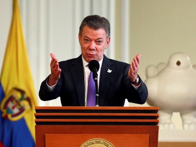 Colombia's President Juan Manuel Santos acknowledges the applause while addressing people who worked for the peace accord to be approved in the recent referendum, after winning the Nobel Peace Prize.