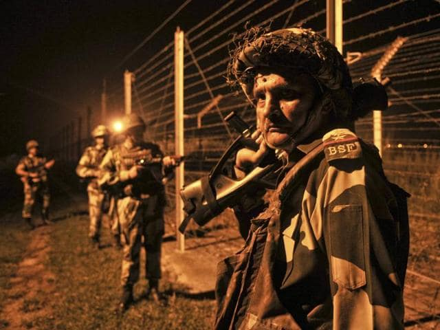 BSF soldiers standing guard during a night patrol near the fence at the India-Pakistan border at Akhnoor.