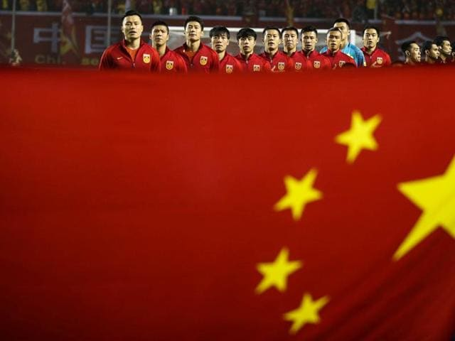 Team China listen to national anthem behind a Chinese national flag ahead of a match.