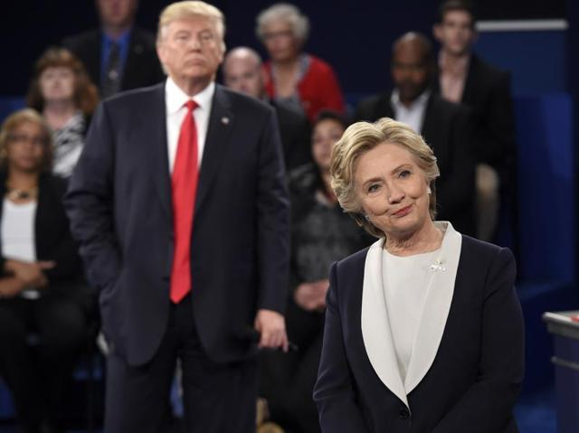 Republican US presidential nominee Donald Trump looks on as Democratic US presidential nominee Hillary Clinton speaks during their presidential town hall debate at Washington University in St. Louis.