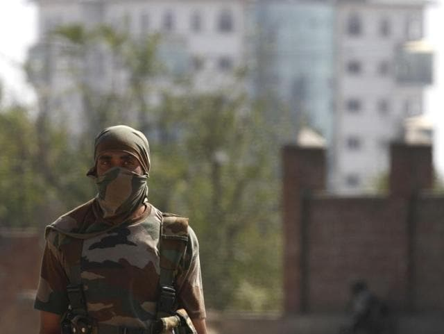 A soldier stands guard near the government building in Pampore where militants have taken refuge during a gun-battle.