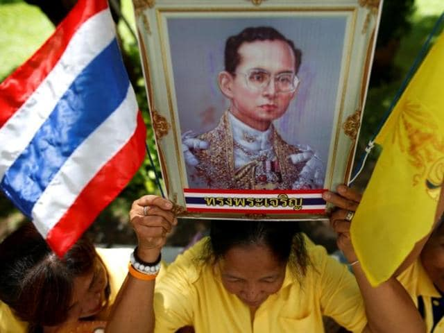 A well-wisher holds a picture of Thailand's King Bhumibol Adulyadej at the Siriraj hospital where he is residing, in Bangkok.