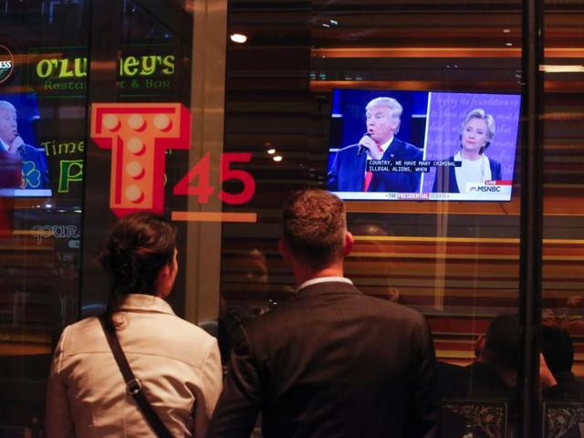 People watch the second presidential debate between US Democratic presidential candidate Hillary Clinton and US Republican presidential candidate Donald Trump outside a restaurant near Times Square in New York on October 9, 2016.