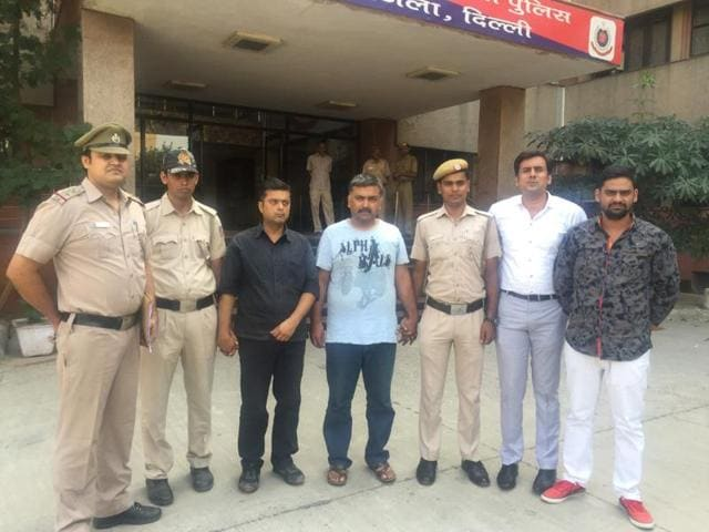 The two men (centre) arrested for blackmailing a woman with police.