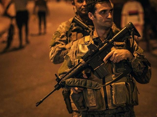 Officers of the special police unit (BOPE) patrol the street following clashes between drug dealers inside the Pavao-Pavaozinho favela -between Copacabana and Ipanema- in Rio de Janeiro on Monday. The Pacifying Police Unit (UPP) was attacked during the gunfights and the commander was injured .