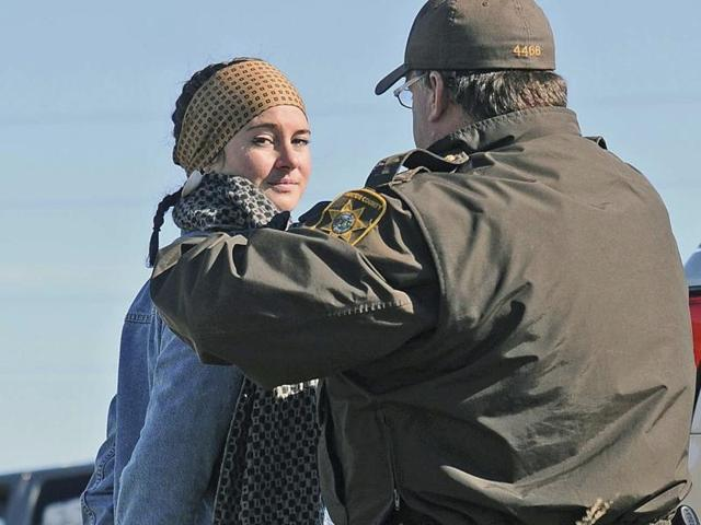 Actress Shailene Woodley is led to a transport vehicle by a Morton County Sheriff's deputy after being arrested at a protest against the Dakota Access Pipeline.