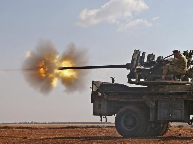 Fighters from the Free Syrian Army fire an anti-aircraft machine gun mounted on a vehicle deploy during fighting against the Islamic State (IS) jihadists in the northern Syrian village of Yahmoul in the Marj Dabiq.