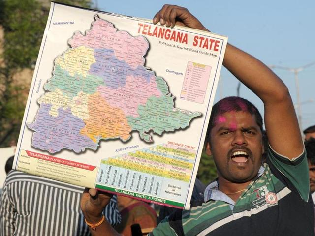 A TRS supporter holds a map of Telangana state in Hyderabad.