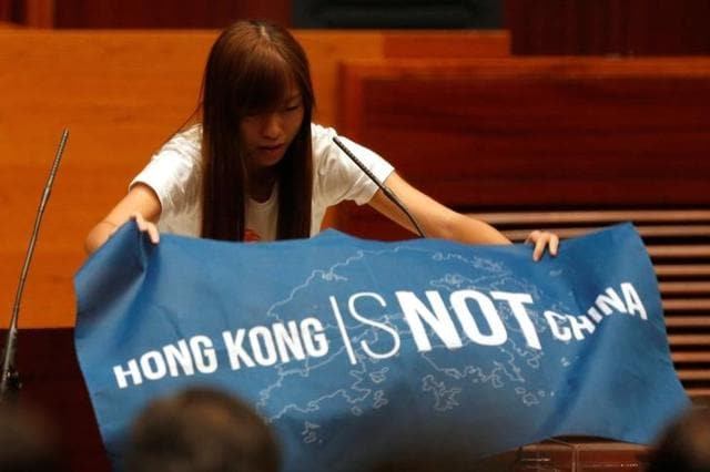 Newly elected lawmaker Yau Wai-ching displays a banner before taking oath at the Legislative Council in Hong Kong, China.