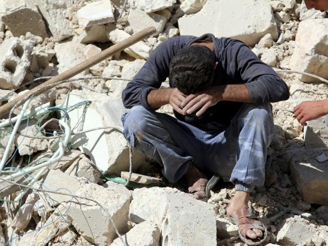 A man reacts on the rubble of damaged buildings after losing relatives to an airstrike in the besieged rebel-held al-Qaterji neighbourhood of Aleppo on Tuesday.