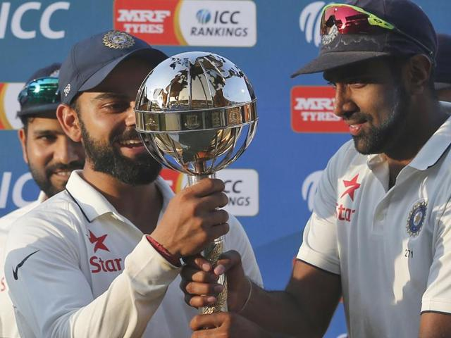 Indian cricket team captain Virat Kohli, left, and teammate Ravichandran Ashwin hold the ICC Test Championship mace at the end of their third test cricket match against New Zealand in Indore, India, Tuesday, Oct. 11, 2016.