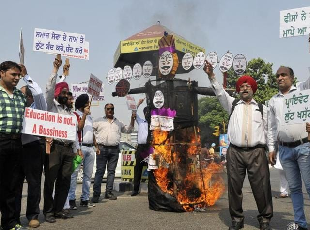 Members of parents' association burning the effigy of school mafia at Bharat Nagar Chowk in Ludhiana on Tuesday.
