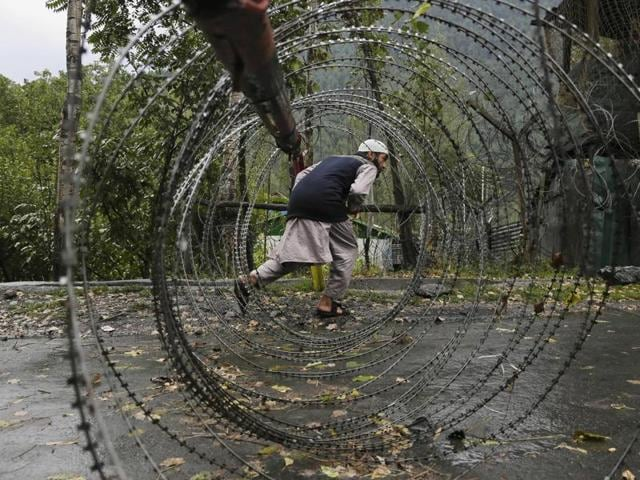 A Kashmiri man ducks to cross an iron barricade with coils of razor wire near a military base in Kashmir.