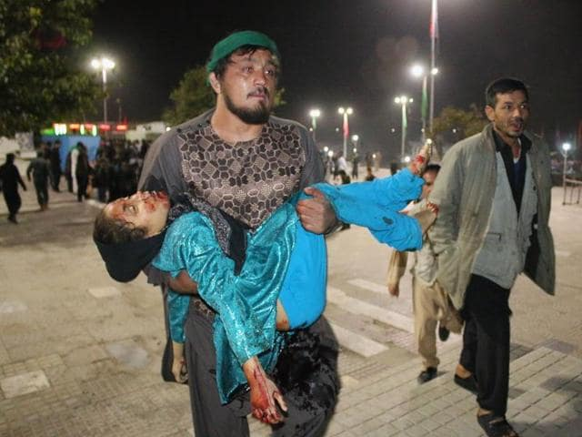 Afghan man carrying a wounded girl after an attack by gunmen at the Karte Sakhi shrine in Kabul on Tuesday.