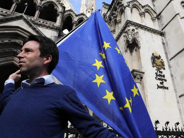 A pro-European Union supporter holds up a banner outside Britain's High Court in London on Thursday during a protest against the UK's decision to leave the EU. The battle over Britain's exit from the EU reached the High Court in a legal challenge to Prime Minister Theresa May's right to start negotiations for Britain to leave the EU without a vote in Parliament.