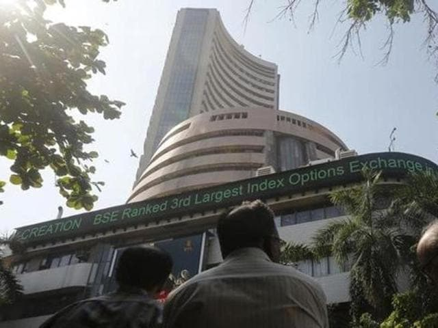 People watch a large screen displaying Sensex on the facade of the Bombay Stock Exchange (BSE) building in Mumbai.