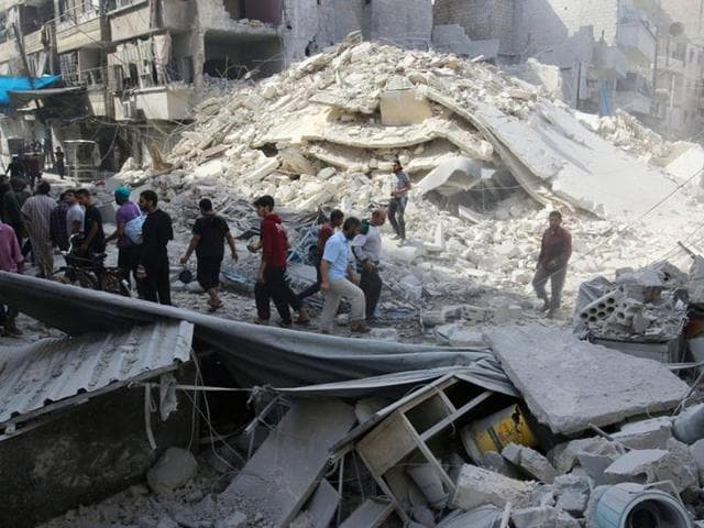 People inspect the damage at a market hit by airstrikes in Aleppo's rebel held al-Fardous district, Syria.
