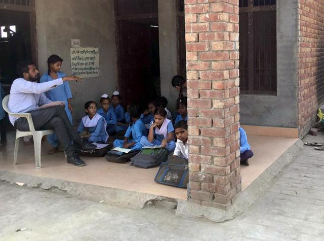 Class 5 students sitting on the floor while a worker preparing mid-day meal for students in the open at the government elementary school at Kuka village near Patiala on Wednesday.