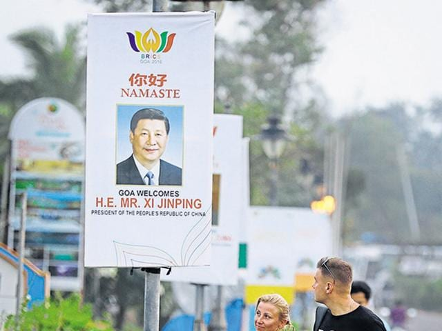 A Russian tourist couple walks past the BRICS poster of Chinese President Xi Jinping, in Goa, on Thursday.