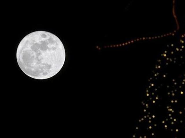 A full moon rises in the sky over a Christmas tree in Beirut, Lebanon.