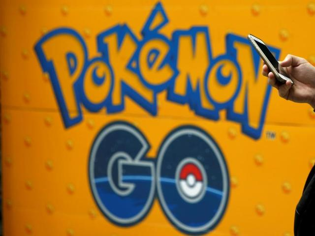 A man uses a mobile phone in front of an advertisement board bearing the image of Pokemon Go at an electronic shop in Tokyo, Japan.