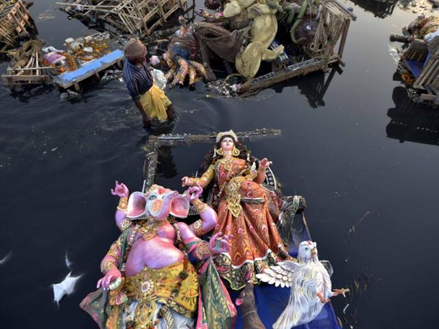 Locals scavenge for the remains of idols after Durga Puja immersion in the Yamuna near ISBT, New Delhi on Wednesday