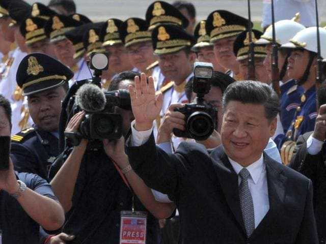 Chinese President Xi Jinping waves to Cambodian students and officials before departing from Phnom Penh international airport on Friday.