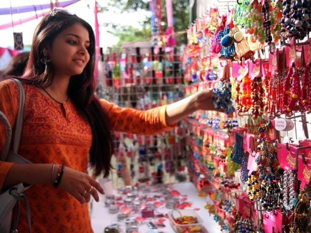 Girl buys earrings from one of the most colourful stalls at The Lady Shri Ram College Diwali Mela.