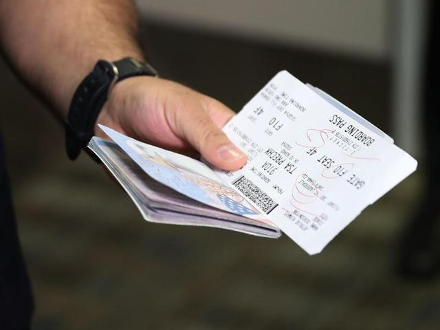 A passenger holds his passport and ticket at the Fort Lauderdale-Hollywood International Airport in Florida.
