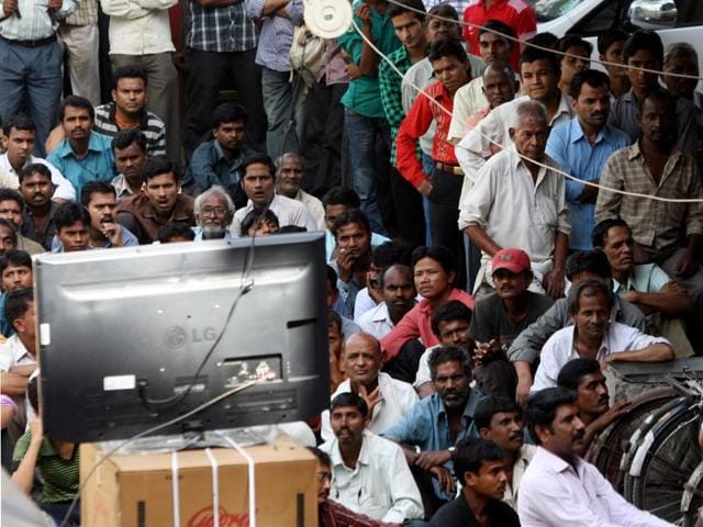 People watch a cricket match on TV outside an electronics store in Mumbai's Ghatkopar. The TV industry has boomed in India, but the pressure to earn profits is great.(Rajendra Gawankar/ HT file photo)