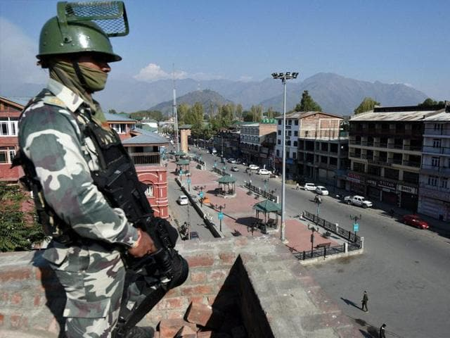 A soldier keeps vigil from top of a building at Lal Chowk during a strike in Srinagar.