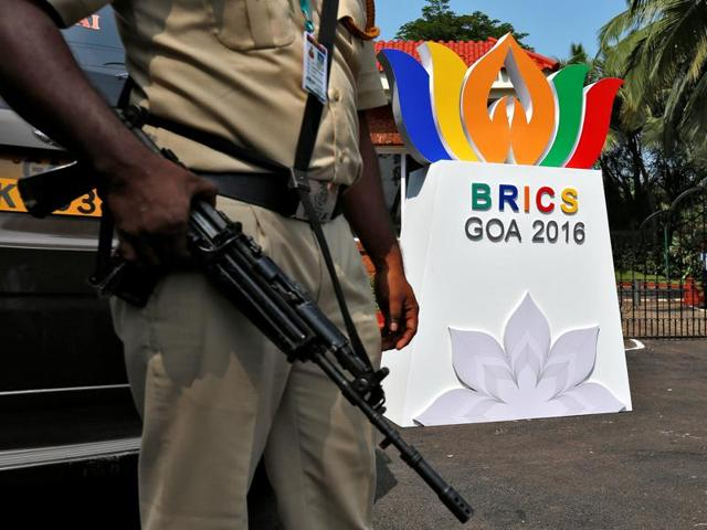 A man rides past a billboard near one of the venues of BRICS Summit in Goa.