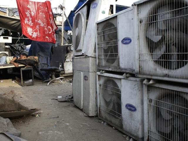 In this file photo, a boy sleeps near an air conditioner shop at a marketplace in New Delhi. Nations reached a deal Saturday to limit the use of hydrofluorocarbons, or HFCs - greenhouse gases far more powerful than carbon dioxide that are used in air conditioners and refrigerators, in a major effort to fight climate change.