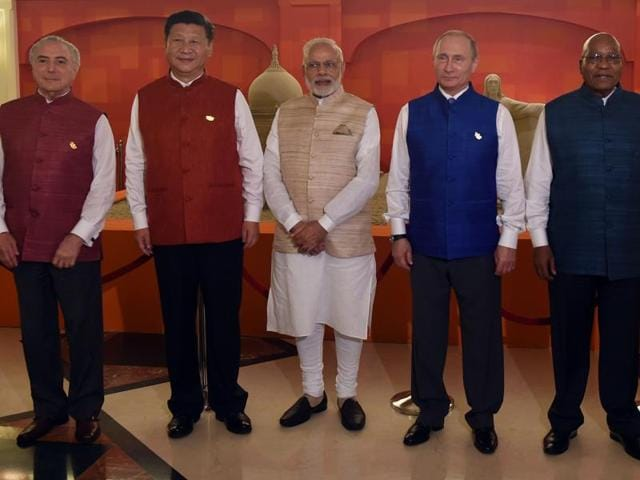 Heads of all the participating nations pose in front of sand art representing national monuments from BRICS member countries ahead of an informal dinner during the BRICS summit in Goa.