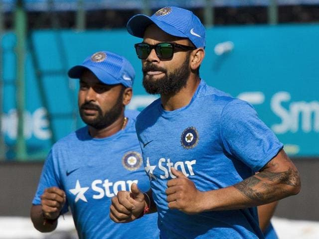 India's Virat Kohli, right, and Amit Mishra run during a practice session at the Himachal Pradesh Cricket Association stadium in Dharamsala.