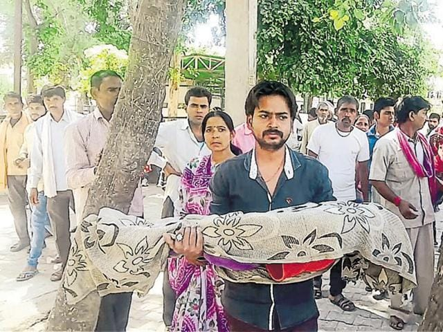 Pawan Namdev with the body of his six-year-old son Anuj in Bhind.