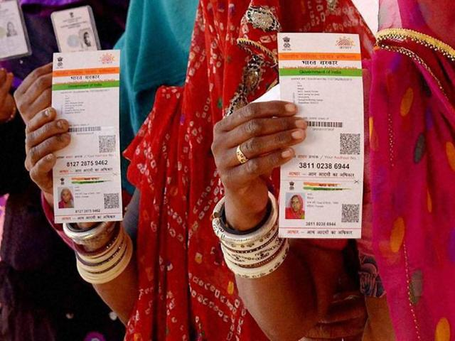 Women show their Aadhaar cards while standing in a queue at a poll booth in Ajmer.
